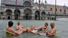 People sit at a table in flooded St Mark's Square
