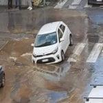 Cede l'asfalto, auto intrappolata in centro